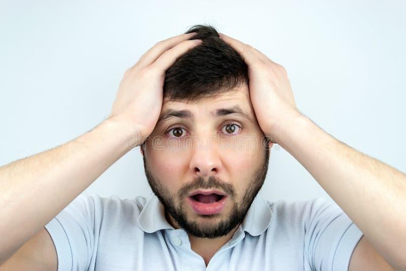 Hombre barbudo sorprendido con los ojos y boca abierta de par en par, llevando a cabo su cabeza con sus manos, en una camiseta bl imágenes de archivo libres de regalías