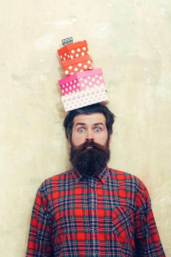 Hombre barbudo sorprendido que sostiene las cajas de regalo coloridas apiladas en la cabeza imagen de archivo