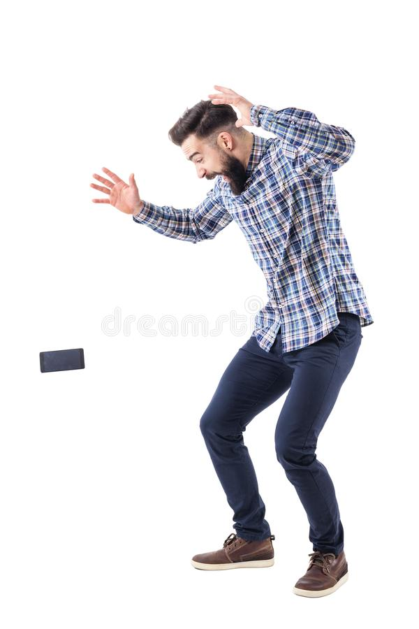 Hombre barbudo torpe descuidado chocado que cae el teléfono móvil que cae en la tierra en mediados de aire foto de archivo
