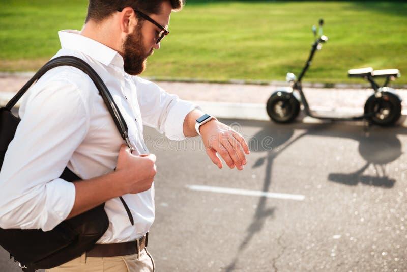 Hombre barbudo tranquilo en las gafas de sol que sostienen la mochila imágenes de archivo libres de regalías