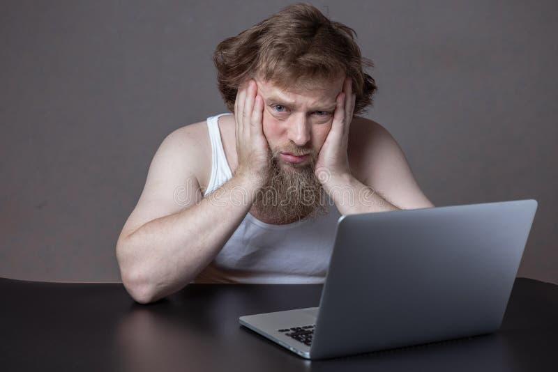 Hombre barbudo trastornado en la camisa que se sienta al lado del cuaderno Sirva la cabeza del control por dos manos y mire en cu foto de archivo libre de regalías
