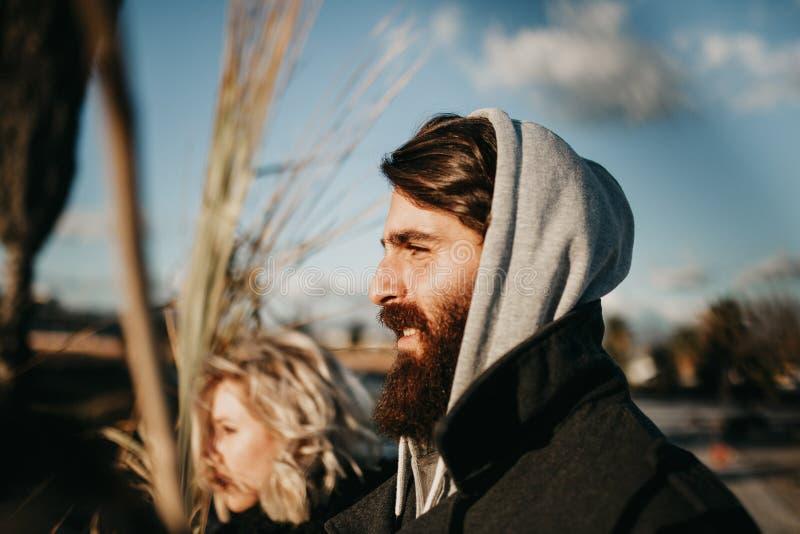 Hombre barbudo y mujer rubia que presentan en la puesta del sol con las ramas de palmera imagenes de archivo