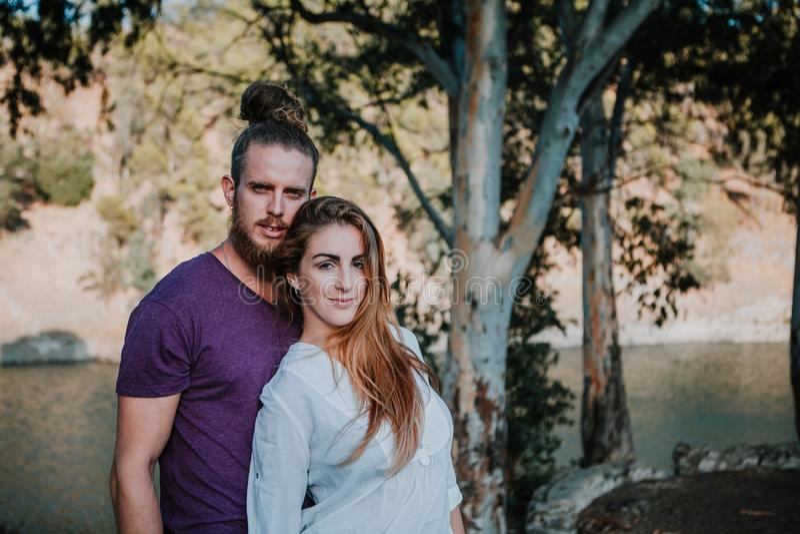Hombre barbudo y mujer rubia que presentan junto de una manera romántica en naturaleza foto de archivo