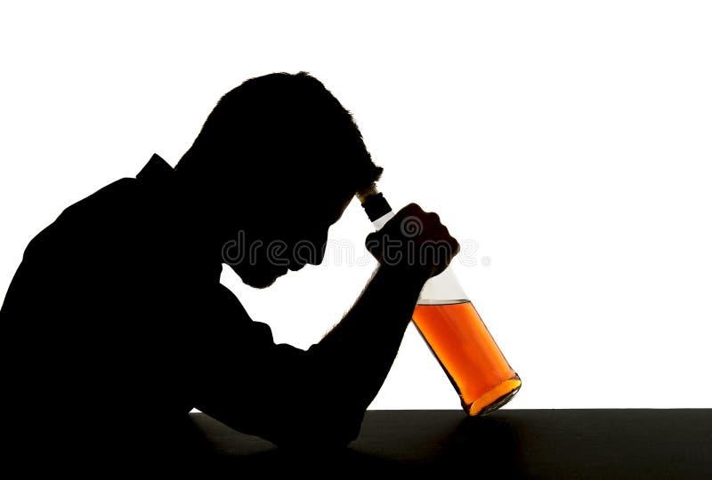 Hombre bebido alcohólico con la botella de whisky en silueta de la adicción al alcohol imagenes de archivo