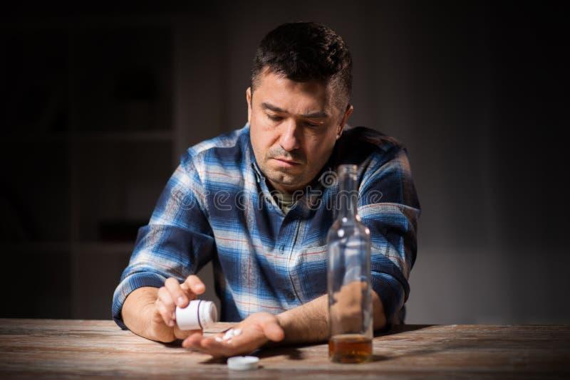 Hombre bebido infeliz con la botella de alcohol y de píldoras fotografía de archivo libre de regalías
