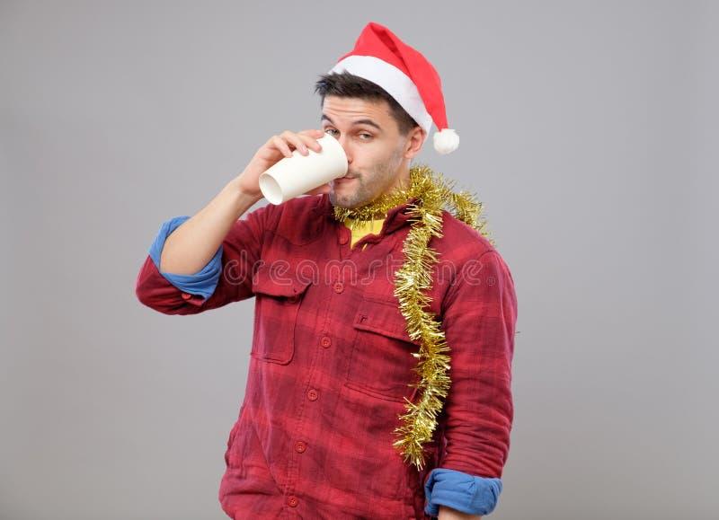 Hombre bebido joven divertido que lleva el sombrero de Papá Noel que sostiene una taza de papel fotografía de archivo libre de regalías