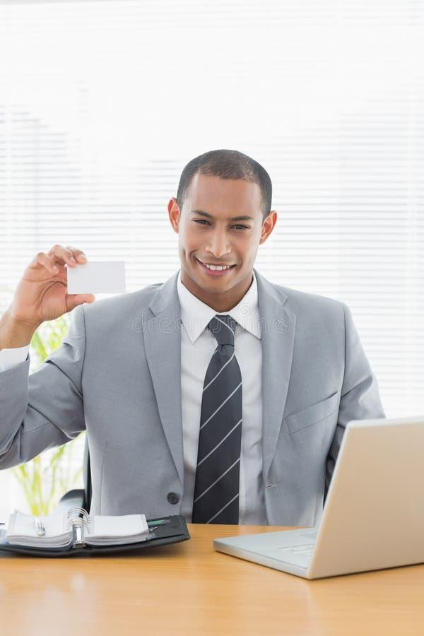 Hombre bien vestido confiado con la tarjeta de visita en el escritorio de oficina foto de archivo libre de regalías