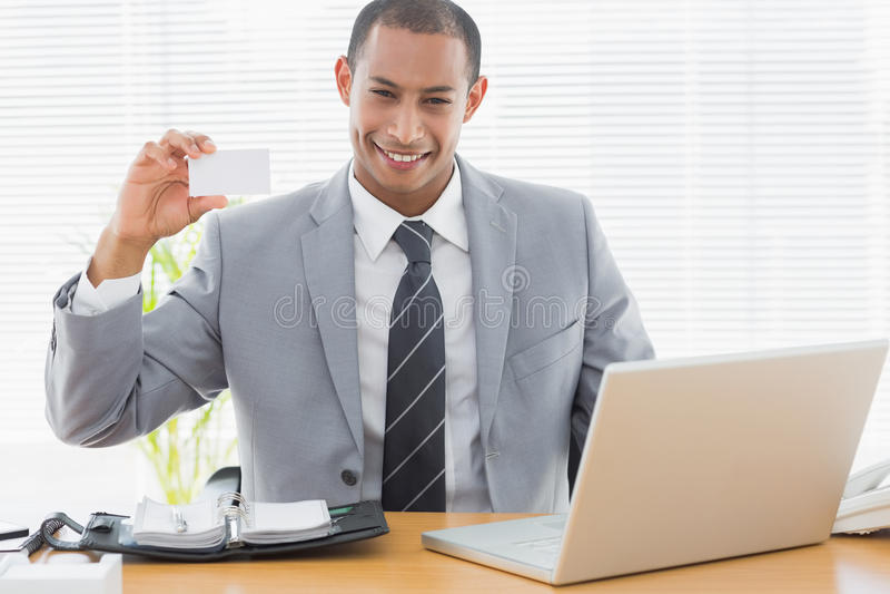 Hombre bien vestido confiado con la tarjeta de visita en el escritorio de oficina imágenes de archivo libres de regalías