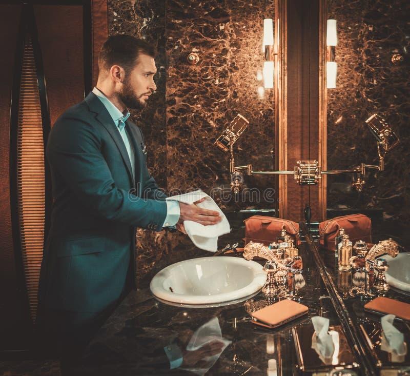 Hombre bien vestido confiado en interior de lujo del cuarto de baño foto de archivo libre de regalías