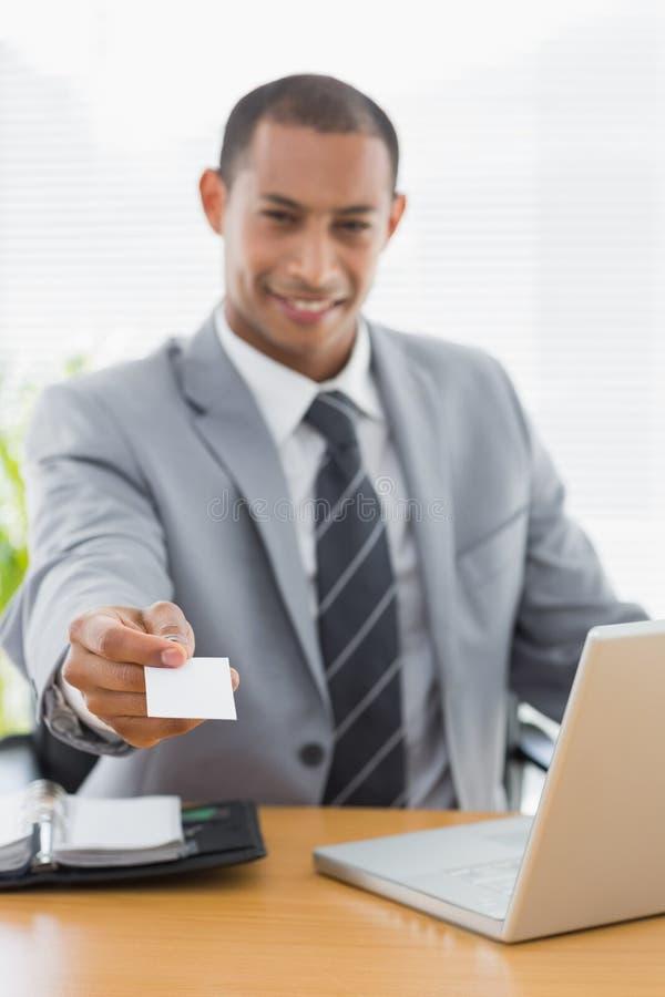 Hombre bien vestido que da su tarjeta de visita en el escritorio de oficina fotografía de archivo libre de regalías
