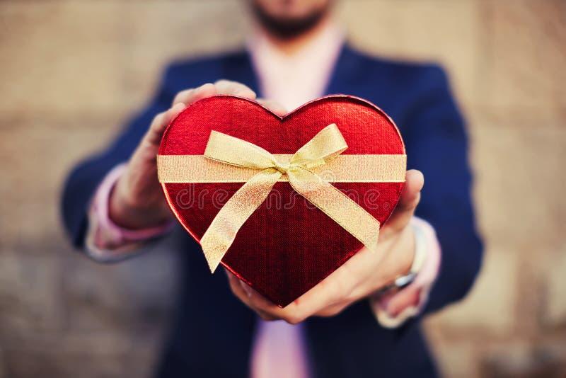 Hombre bien vestido que sostiene una caja de regalo en forma de corazón el día de madre imagen de archivo