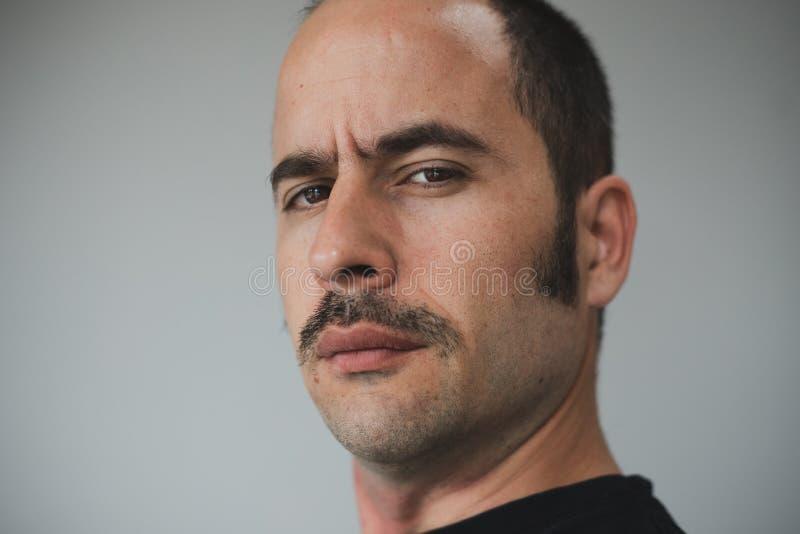 Hombre blanco con un bigote prominente que mira derecho la cámara imagen de archivo libre de regalías