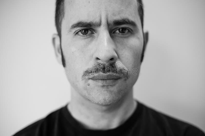 Hombre blanco con un bigote prominente que mira derecho la cámara foto de archivo