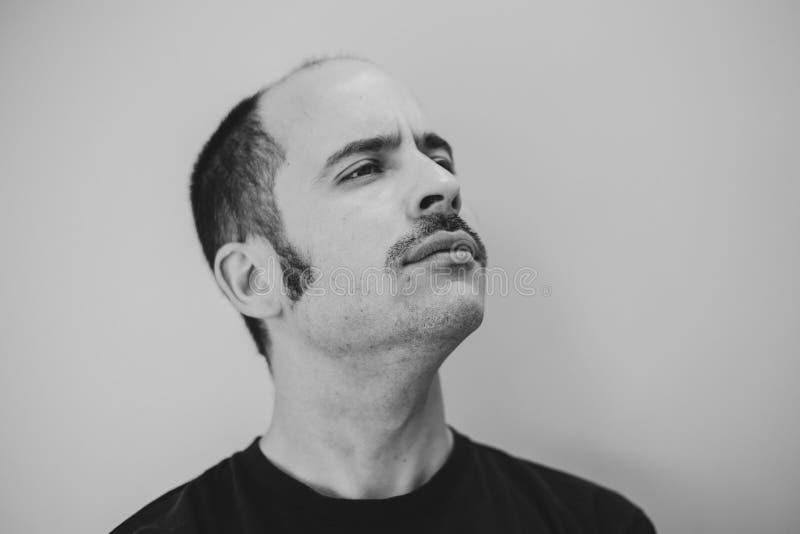 Hombre blanco con un bigote prominente que mira en la distancia imagenes de archivo