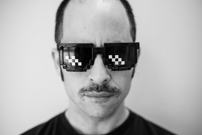 Hombre blanco con un bigote prominente y vidrios divertidos que miran derecho la cámara imagen de archivo libre de regalías