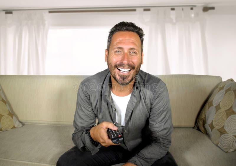 Hombre blanco hermoso y feliz 30s o 40s que mira la risa hilarante del programa de televisión en casa alegre teniendo sentarse de imagen de archivo