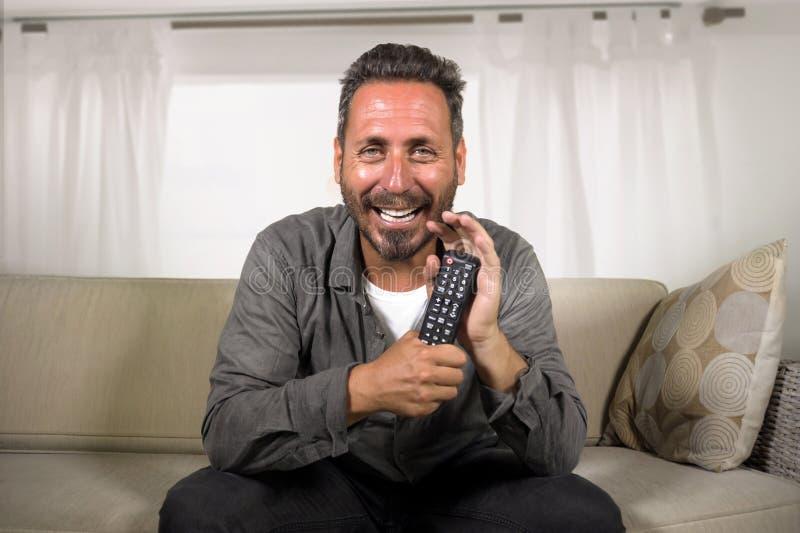 Hombre blanco hermoso y feliz 30s o 40s que mira la risa hilarante del programa de televisi?n en casa alegre teniendo sentarse de imagen de archivo