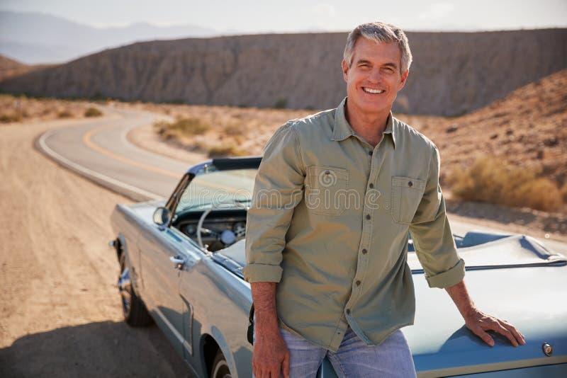 Hombre blanco mayor que se inclina en el coche de tragante abierto en el borde de la carretera del desierto imagenes de archivo
