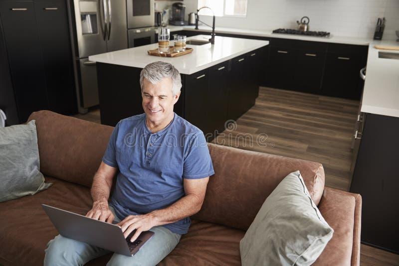 Hombre blanco mayor que se sienta en el sofá usando el ordenador portátil, visión elevada fotos de archivo