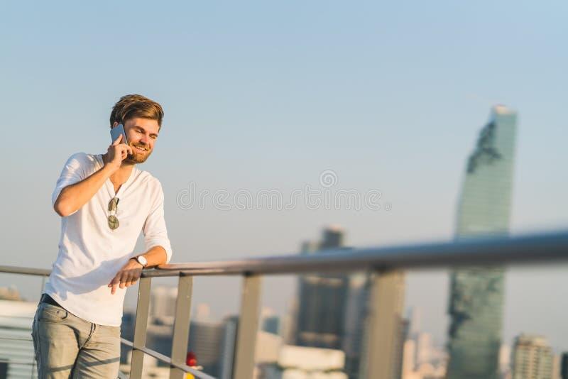Hombre blanco que usa el teléfono móvil en el tejado durante la puesta del sol, sonriendo mientras que en llamada de teléfono Tec fotografía de archivo