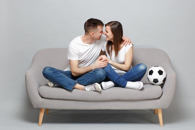 Hombre bonito de la mujer de los pares que los fanáticos del fútbol anima para arriba el equipo preferido de la ayuda con el baló foto de archivo libre de regalías