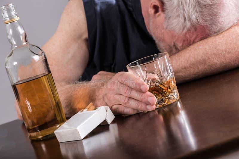 Hombre borracho que duerme en la tabla fotos de archivo