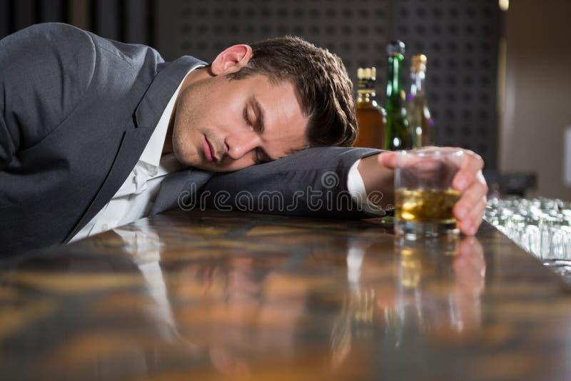 Hombre borracho que miente en un contador con el vidrio de whisky fotografía de archivo libre de regalías