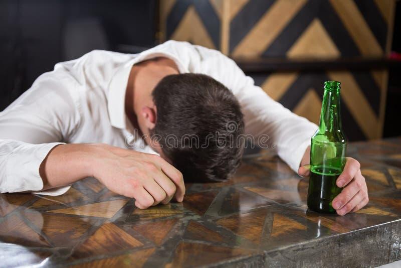 Hombre borracho que miente en un contador con la botella de cerveza foto de archivo