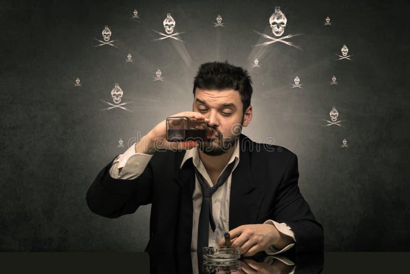 Hombre borracho que se sienta en la tabla con concepto de los cr?neos foto de archivo libre de regalías