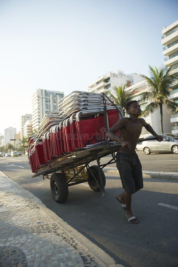 Hombre brasileño joven que tira de las sillas de playa Rio Brazil fotos de archivo libres de regalías