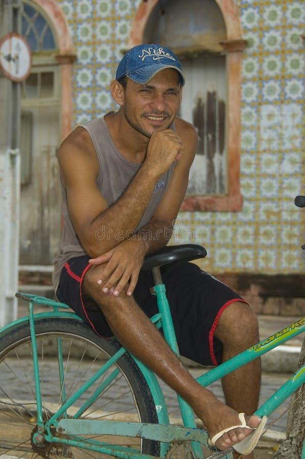 Hombre brasileño que se sienta en su bici delante de su casa fotos de archivo libres de regalías