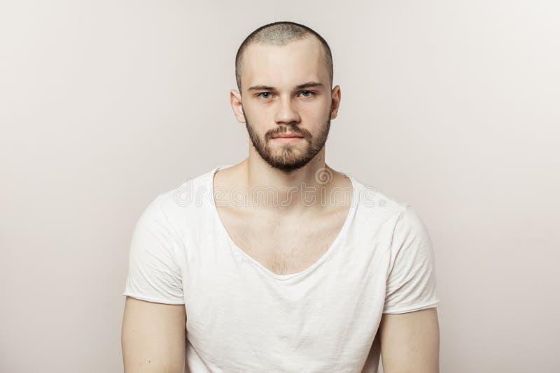Hombre brutal atractivo en la camiseta blanca que mira la cámara fotos de archivo