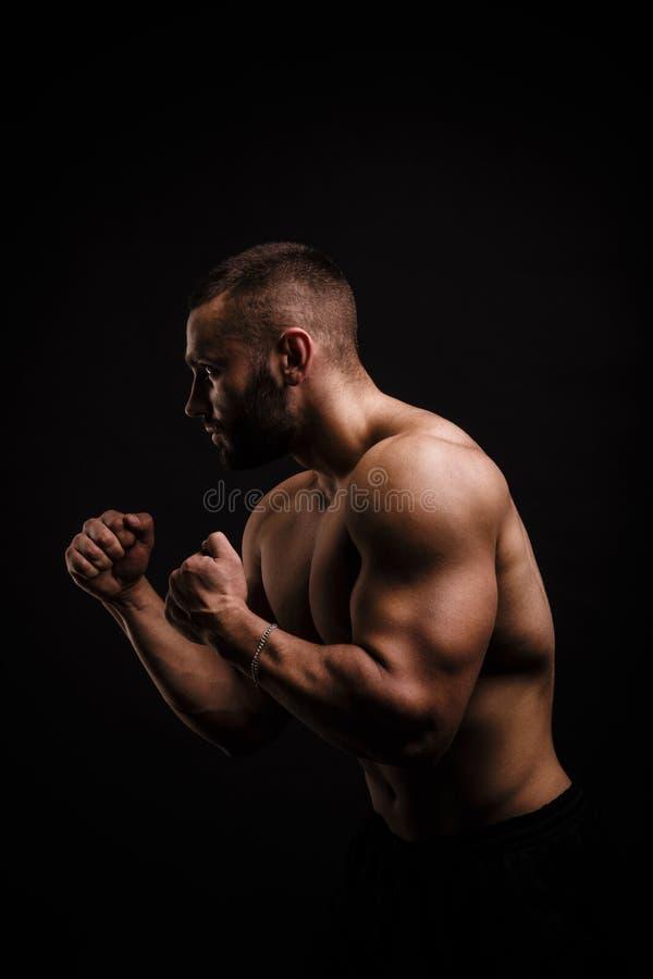 Hombre brutal con el cuerpo muscular perfecto en un fondo negro Entrenamientos atléticos o del levantamiento de pesas Concepto de imagen de archivo