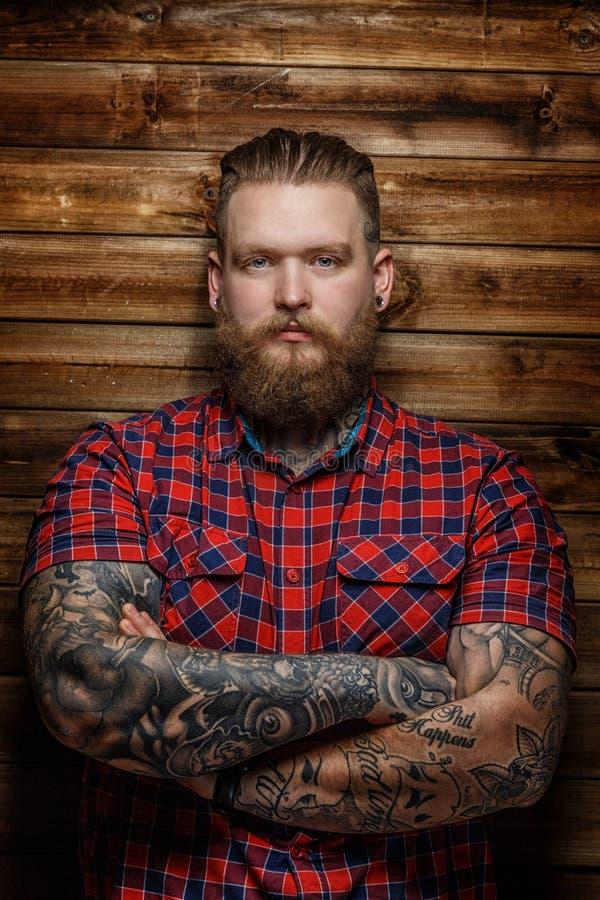 Hombre brutal con los tatuajes y la barba foto de archivo