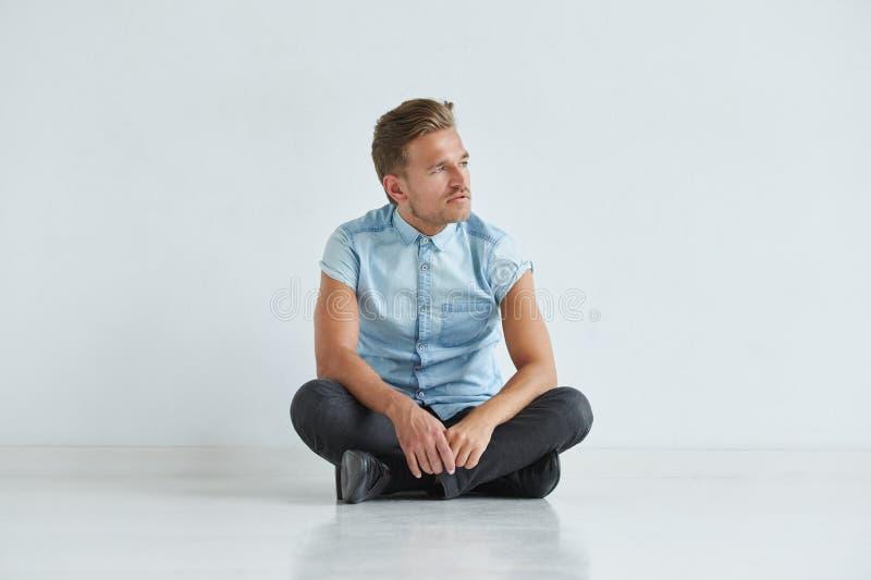 Hombre brutal en una camisa con las mangas cortas que se sientan en postura del loto, fotografía de archivo libre de regalías
