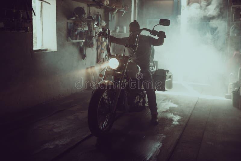 Hombre brutal hermoso con una barba que se sienta en una motocicleta en su garaje imagenes de archivo