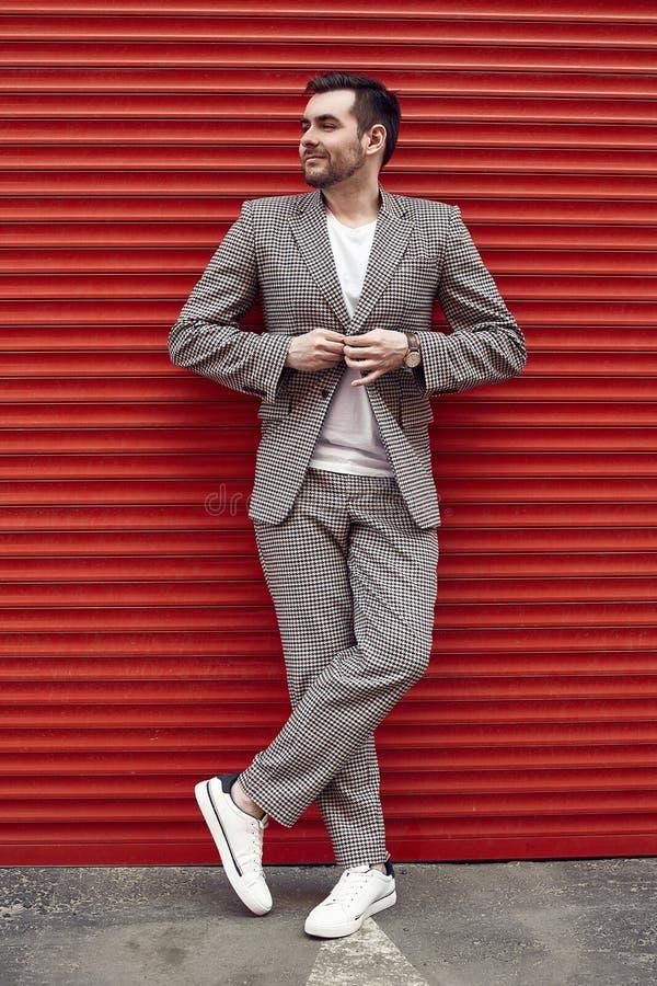 Hombre brutal hermoso joven en un traje de la moda cerca de la puerta roja imagen de archivo libre de regalías