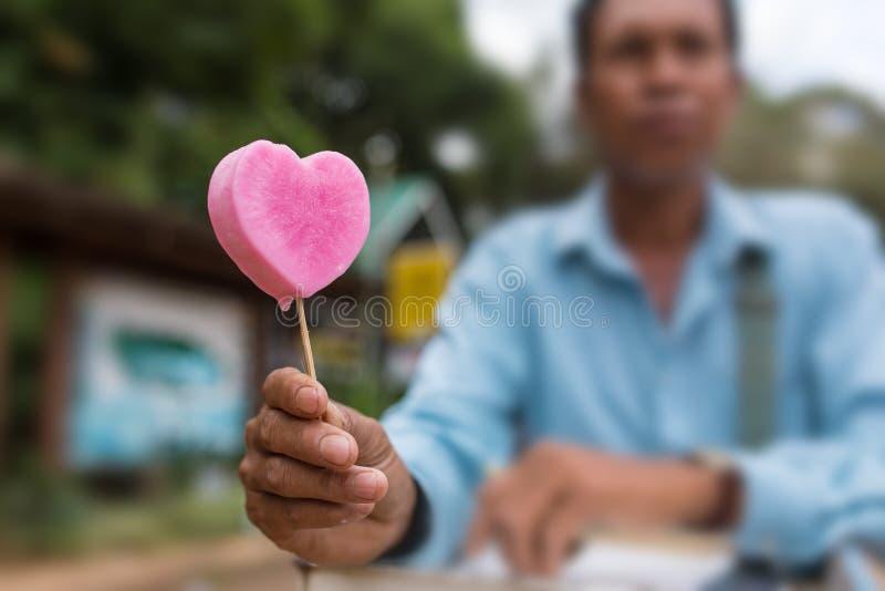 Hombre burmese no identificado que vende el helado rosado en forma del corazón en las calles de Pyin Oo Lwin, Birmania foto de archivo