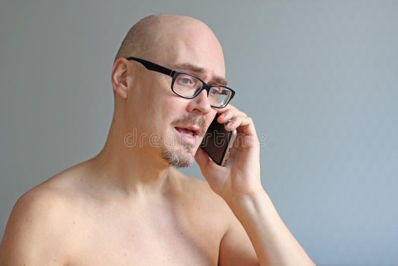 Hombre calvo hermoso joven en vidrios negros que habla en el teléfono Retrato del primer de un hombre Malas noticias, tristeza, p fotos de archivo libres de regalías