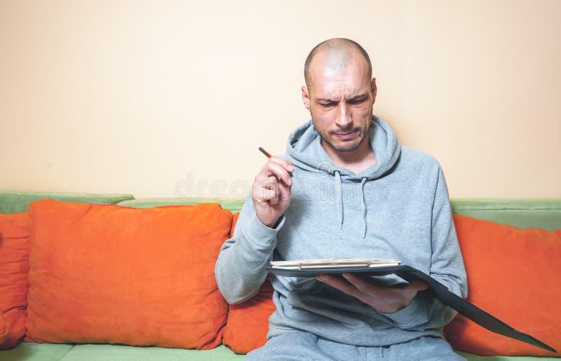 Hombre calvo joven en ropa casual con la expresión facial divertida y confusa que intenta calcular su deuda tributaria del año co fotografía de archivo