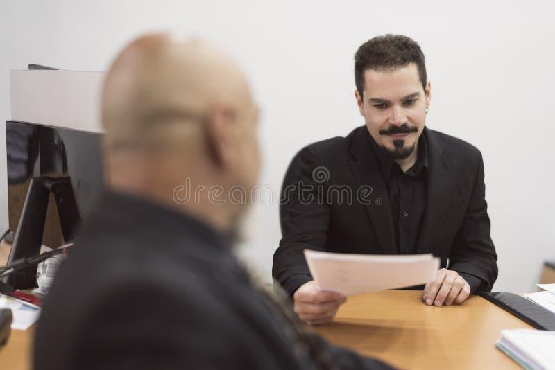 Hombre calvo mayor que trabaja en oficina con el traje negro fotografía de archivo libre de regalías