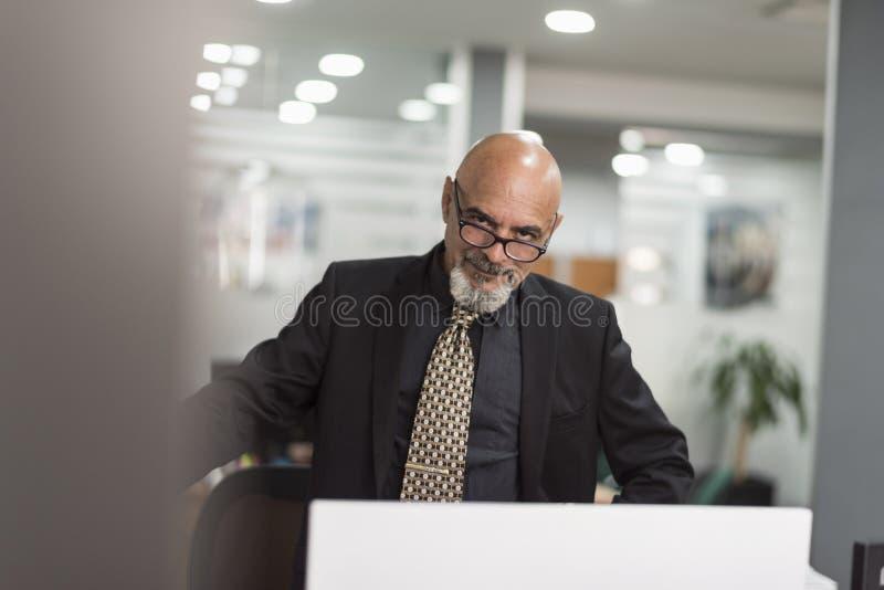 Hombre calvo mayor que trabaja en oficina con el traje negro imagenes de archivo