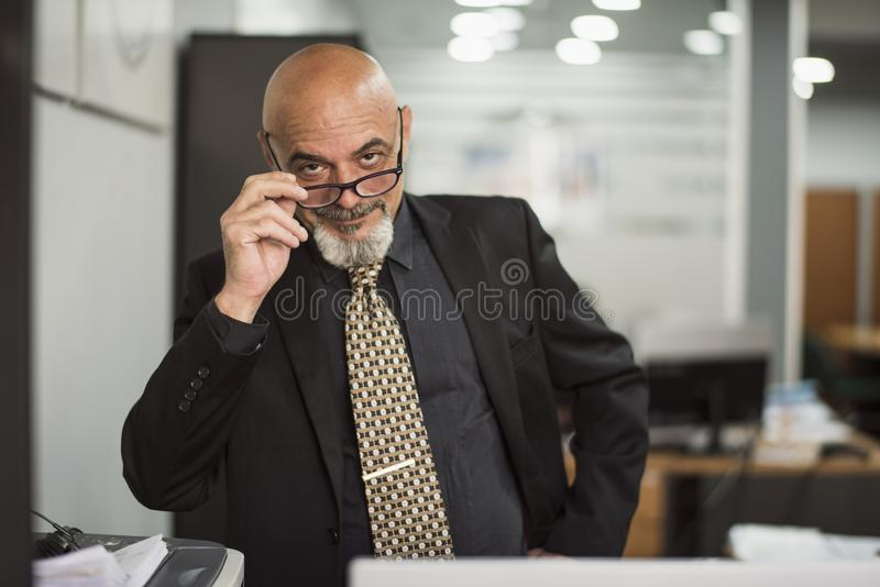Hombre calvo mayor que trabaja en oficina con el traje negro foto de archivo