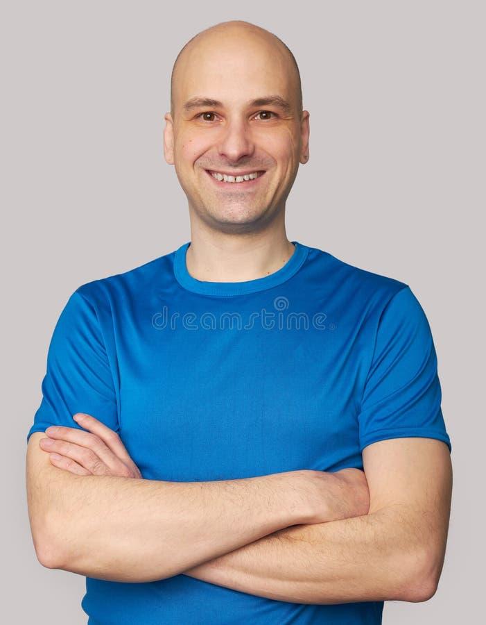 Hombre calvo sonriente que lleva la camiseta azul imágenes de archivo libres de regalías