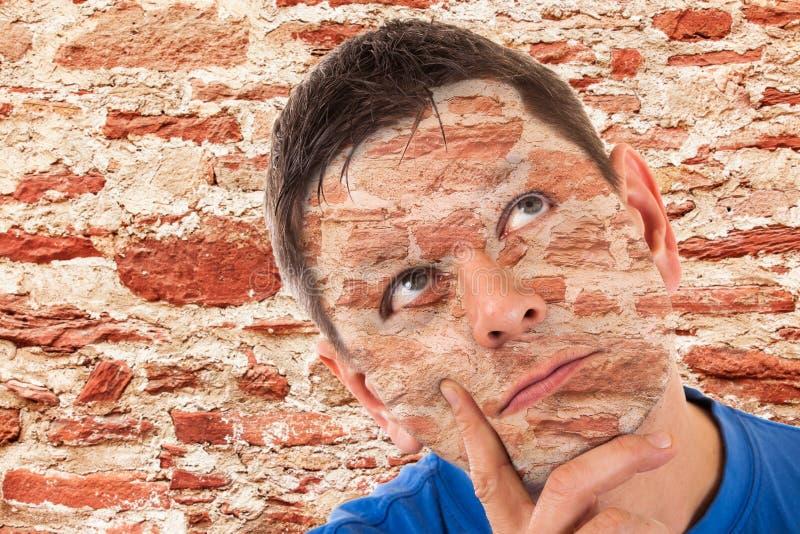 Hombre camuflado delante de una pared fotos de archivo