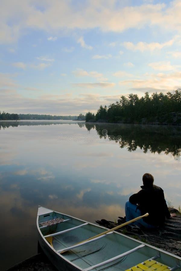 Hombre, canoa y salida del sol imágenes de archivo libres de regalías