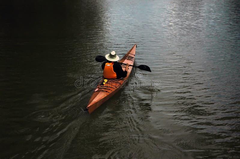 Hombre canoing en el lago imagenes de archivo