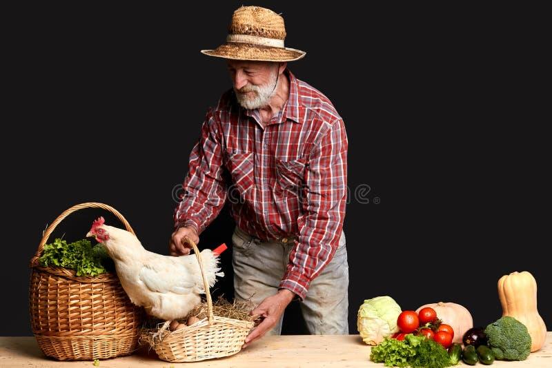 Hombre canoso alegre que va a vender verduras y los huevos de su granja imagenes de archivo