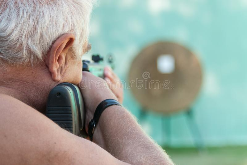 Hombre canoso que apunta de un rifle a una blanco fotos de archivo libres de regalías