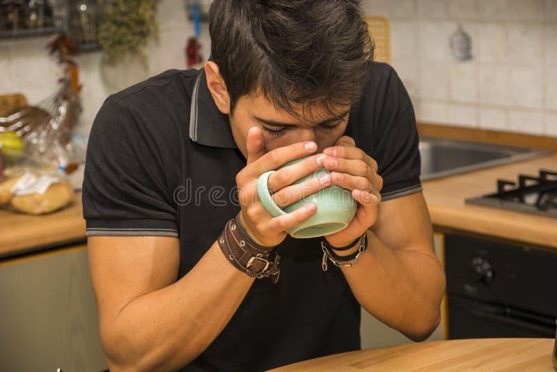 Hombre cansado con el café que se sienta en la tabla de cocina imagen de archivo libre de regalías